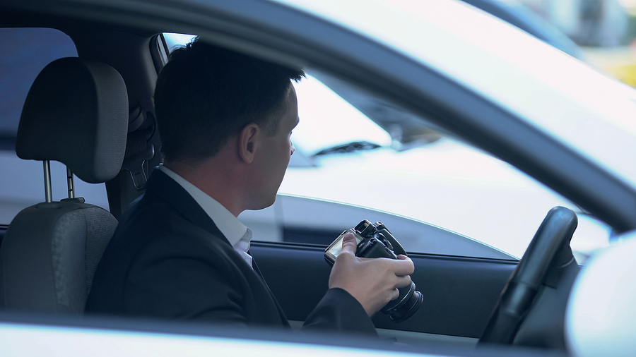 private agent with camera sitting in car, searching for evidence of cheating